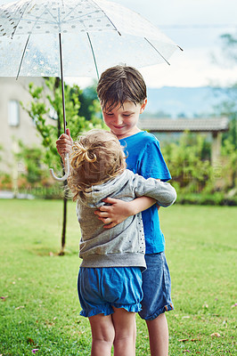 Buy stock photo Shot of a cheerful little boy and girl standing together under an umbrella outside during a rainy day