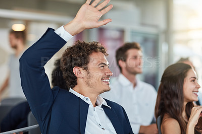 Buy stock photo Cropped shot of a handsome young businessman raising his hand during a seminar