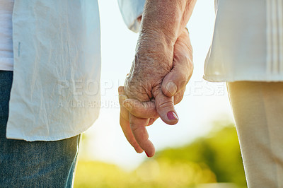 Buy stock photo Cropped shot of a senior couple holding hands in a park