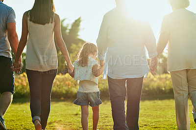 Buy stock photo Rearview shot of a family going for a walk together in the park
