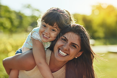 Buy stock photo Shot of an adorable little girl and her mother enjoying a piggyback ride in the park