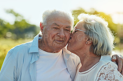 Buy stock photo Shot of a senior woman lovingly kissing her husband on the cheek at the park