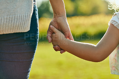 Buy stock photo Cropped shot of a little girl holding an unrecognizable woman's hand in the park