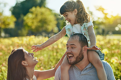 Buy stock photo Shot of an adorable little girl and her parents spending quality time together in the park