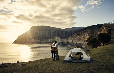 Buy stock photo Rearview shot of an affectionate young couple standing beside their tent while camping in the mountains
