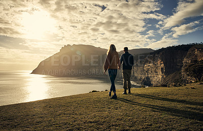 Buy stock photo Rearview shot of an affectionate young couple hiking in the mountains