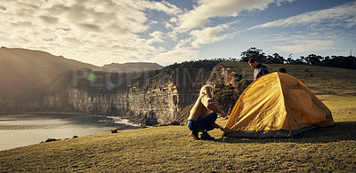 Buy stock photo Shot of an affectionate young couple setting up their tent in the mountains
