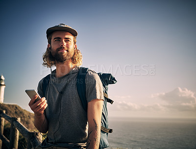 Buy stock photo Shot of a handsome young man listening to music while out on a hike