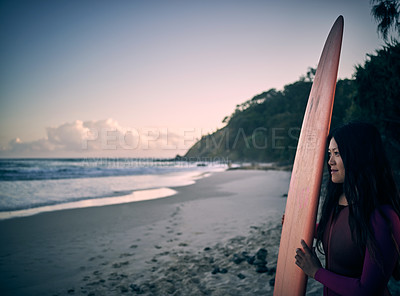 Buy stock photo Shot of an attractive young woman carrying a surfboard at the beach