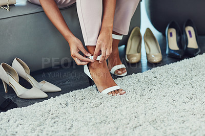 Buy stock photo Shot of an unrecognizable woman trying on shoes while on a shopping spree in a boutique