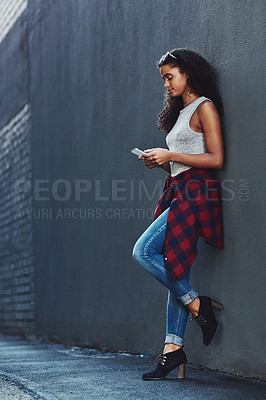 Buy stock photo Shot of an attractive young woman using a cellphone posing against a wall in the city