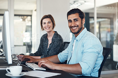 Buy stock photo Portrait of a young businesswoman and businessman sitting next to each other and using their computers in a modern office