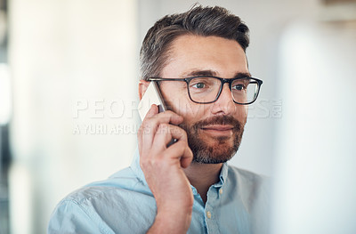 Buy stock photo Shot of a handsome mature businessman using a computer and mobile phone at his desk in a modern office