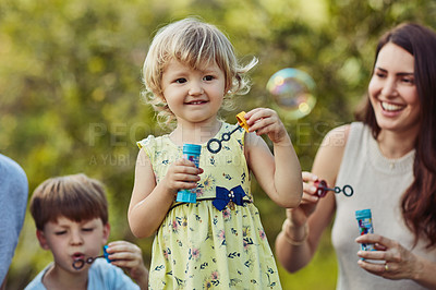 Buy stock photo Shot of an adorable little girl blowing bubbles with her family outdoors