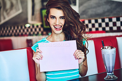 Buy stock photo Cropped portrait of an attractive young woman holding up a sign while enjoying a milkshake in a retro diner