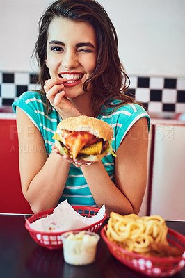 Buy stock photo Cropped portrait of an attractive young woman enjoying a burger in a retro diner