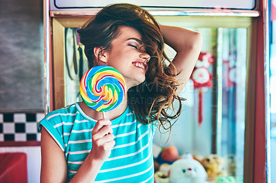 Buy stock photo Cropped shot of an attractive young woman eating a giant lollipop in a retro diner