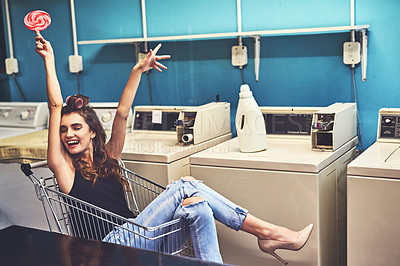 Buy stock photo Shot of an attractive young woman seated inside of a shopping cart while holding a lollipop and lifting her arms in the air inside of a laundry room