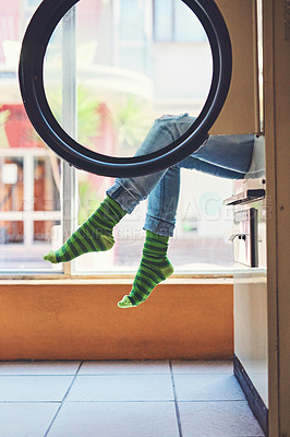 Buy stock photo Shot of an unrecognizable woman seated on a washing machine with her legs showing and showing her bright green striped socks inside of a laundry room