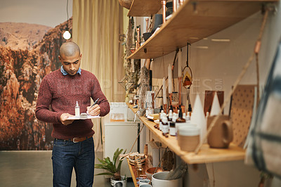 Buy stock photo Shot of a young man conducting inventory in his store