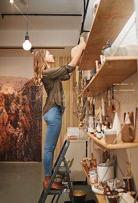 Buy stock photo Shot of a young woman products on the shelves in her store