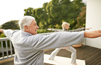 Buy stock photo Cropped shot of a senior married couple practicing yoga at home