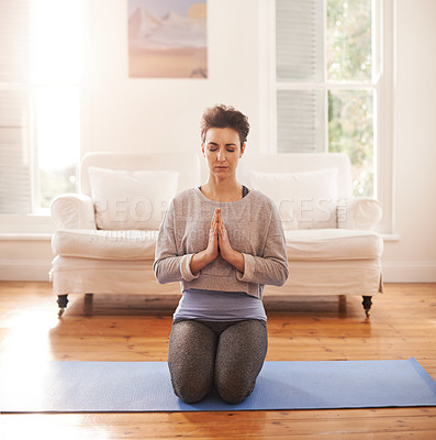 Buy stock photo Shot of an attractive young woman practicing yoga in the living room at home