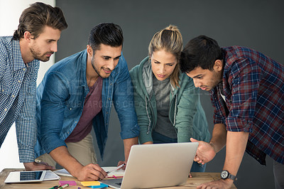 Buy stock photo Shot of a group of designers working together on a laptop in an office