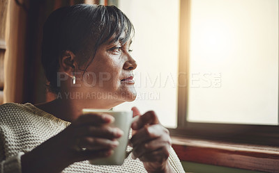 Buy stock photo Shot of a mature woman relaxing with a cup of coffee at home