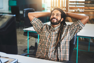 Buy stock photo Cropped shot of a handsome young male designer sitting with his hands behind his head in the office