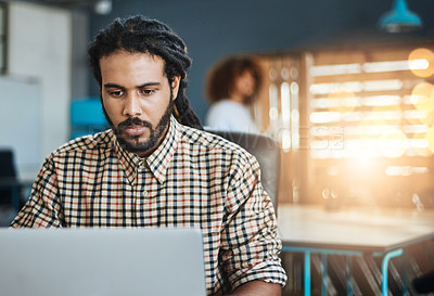 Buy stock photo Cropped shot of a handsome young male designer working on his laptop in the office