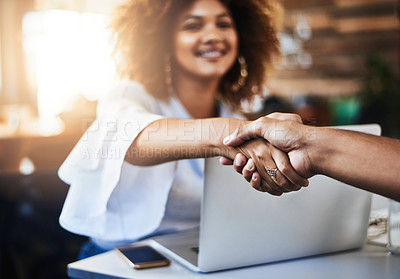 Buy stock photo Cropped shot of two young designers shaking hands while sitting in the office