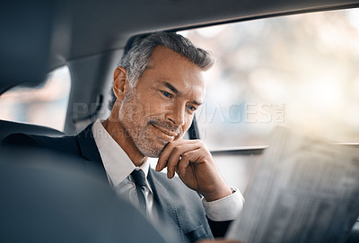 Buy stock photo Cropped shot of a handsome mature businessman reading the paper while sitting in the backseat of a car during his morning commute