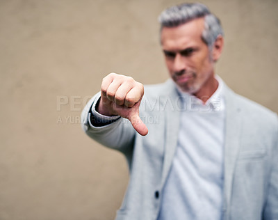 Buy stock photo Cropped shot of a smartly dressed mature businessman showing thumbs down outside