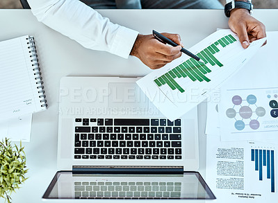 Buy stock photo High angle shot of an unrecognizable businessman going through paperwork while working on a laptop in an office