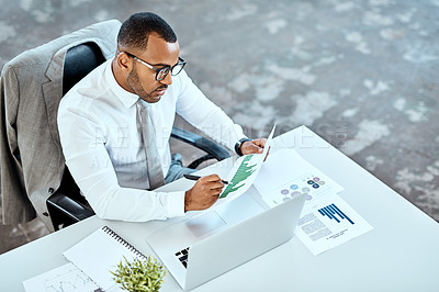 Buy stock photo High angle shot of a young businessman working in an office