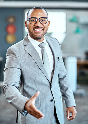 Buy stock photo Portrait of a young businessman extending a handshake in an office
