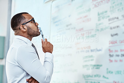 Buy stock photo Shot of a young businessman brainstorming on a whiteboard in an office