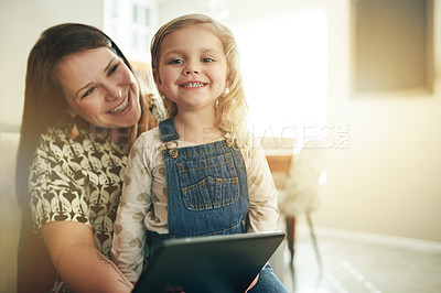 Buy stock photo Shot of a young woman using a digital digital with her daughter at home