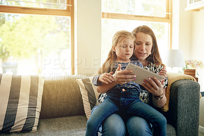 Buy stock photo Shot of young woman using a digital digital with her daughter at home
