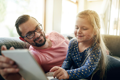 Buy stock photo Shot of young man using a digital digital with his daughter at home