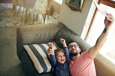 Buy stock photo Shot of a young man taking selfies with his daughter on a digital tablet at home