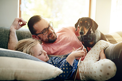 Buy stock photo Shot of a father and his little daughter using a digital tablet together while bonding with their dog at home