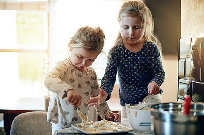 Buy stock photo Shot of two adorable little girls baking together at home