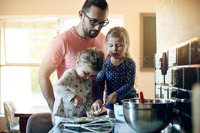 Buy stock photo Shot of a father baking with his two little daughters at home