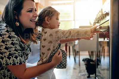 Buy stock photo Shot of a mother and her little daughter using the oven while baking together at home