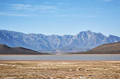 Buy stock photo Shot of a desolate landscape during the day with a small dried out dam in the middle