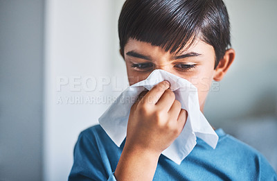 Buy stock photo Cropped shot of an adorable little boy blowing his nose while standing in his home