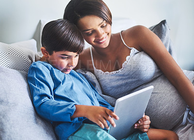 Buy stock photo Cropped shot of an adorable little boy and his pregnant mother using a laptop while relaxing on her bed