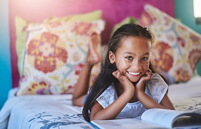 Buy stock photo Portrait of an adorable little girl reading a book at home